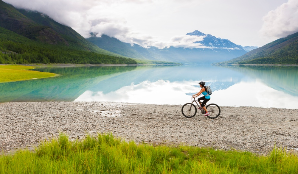 woman riding bicycle near lake, destination to avoid crowds