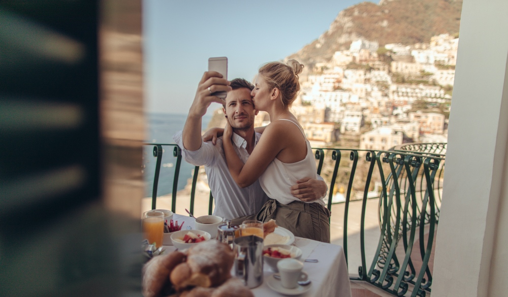 couple having breakfast on the terrace with a view of amazing Positano, Italy