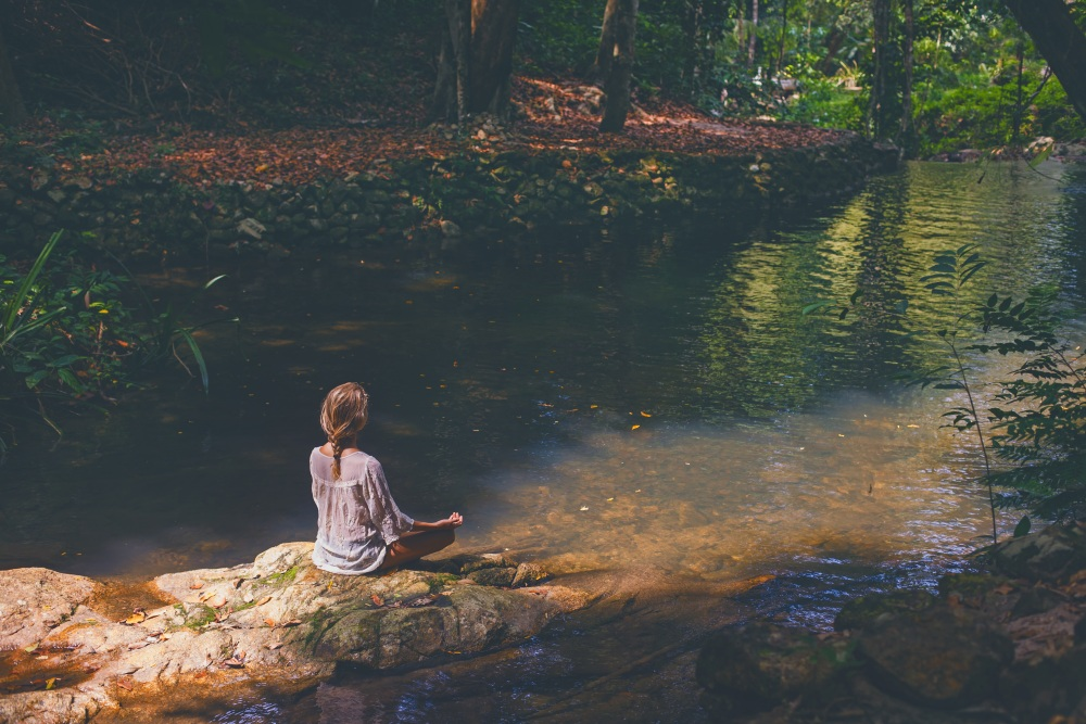 Woman meditating in tropical forest - best yoga retreat