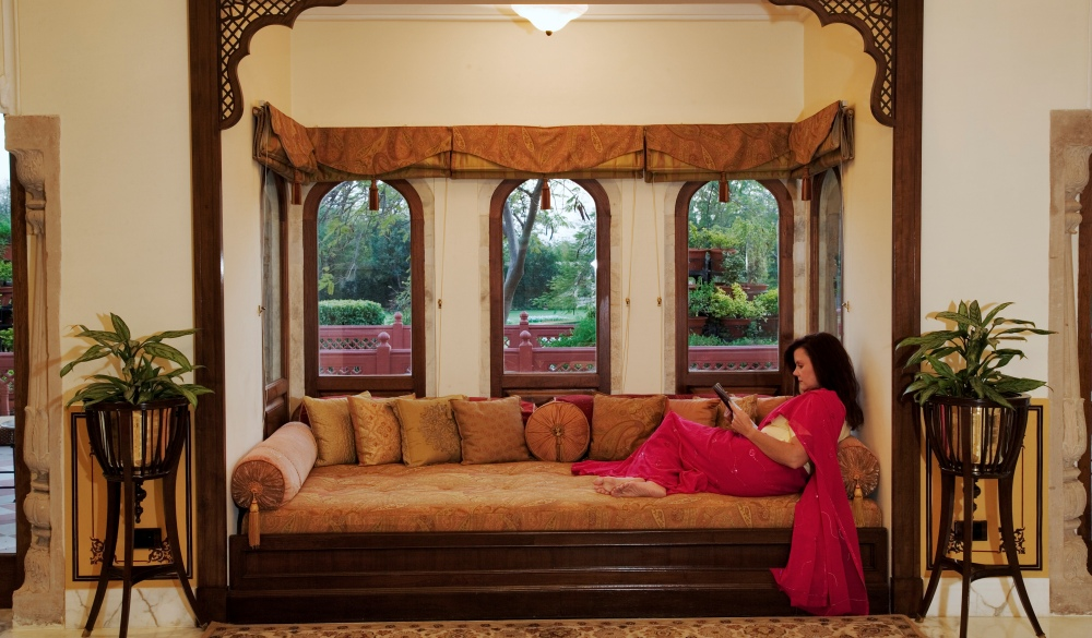 Tourist sitting on couch by bay window of a historical suit in Taj Rambagh Palace Hotel in Jaipur, part of the Taj Hotel Group. India. (MR)