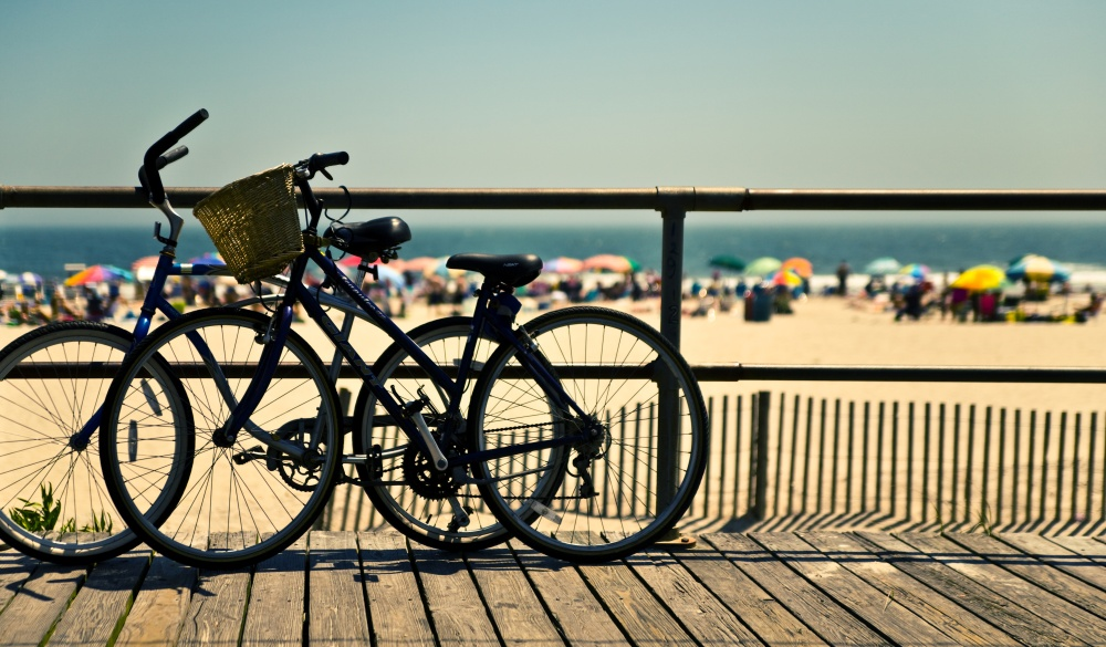 Bicycles in silhouette, propped by the edge of the boardwalk,