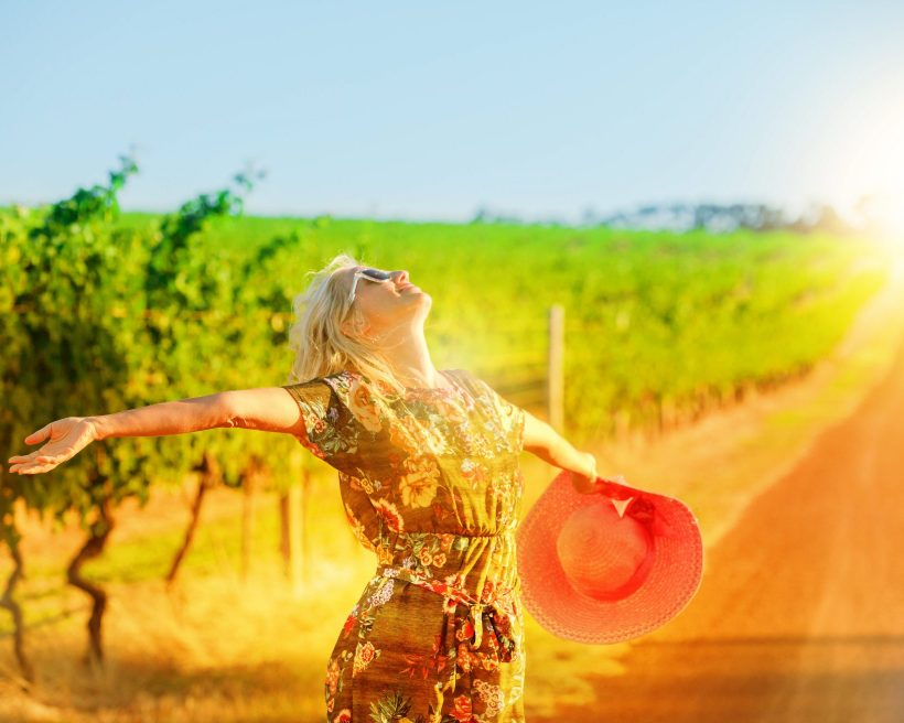 Woman With Arms Outstretched Standing At Vineyard