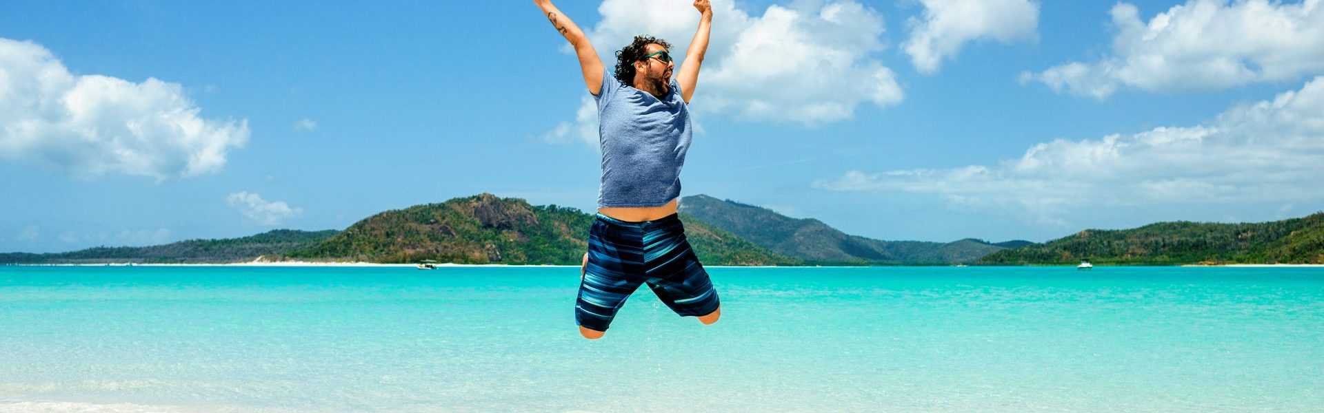 Australia, Queensland, Whitsunday Island, carefree man jumping at Whitehaven Beach
