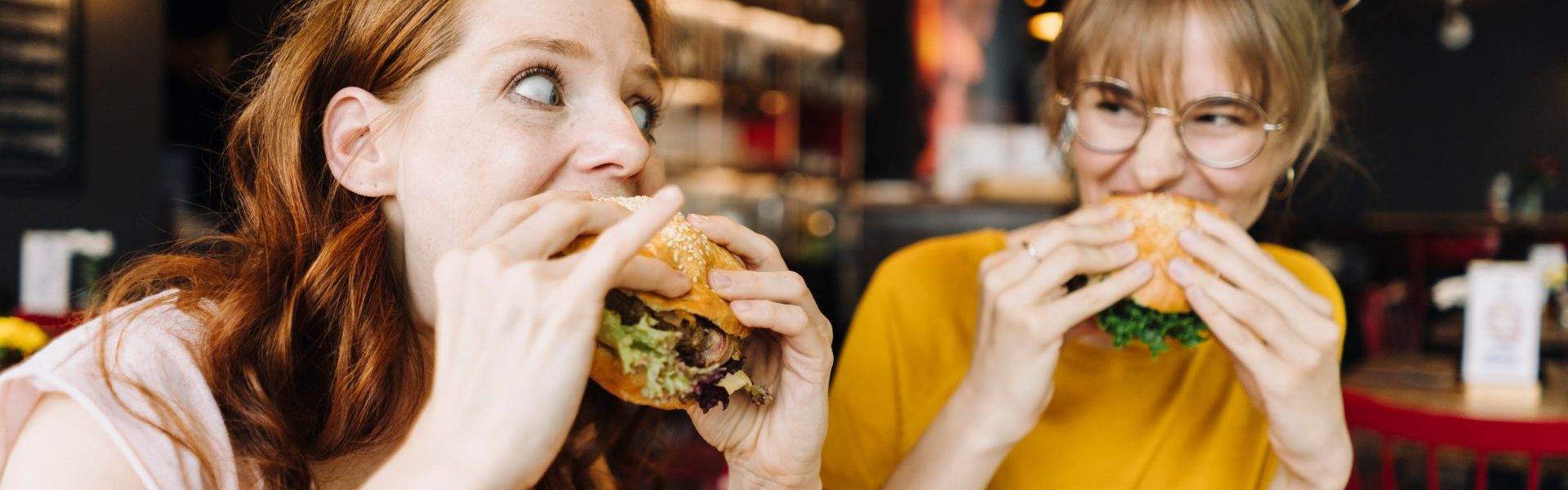 Two female friends eating burger in a restaurant