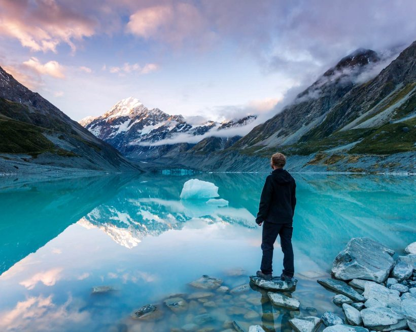 hiker looking at Mt Cook from lake with iceberg, New Zealand