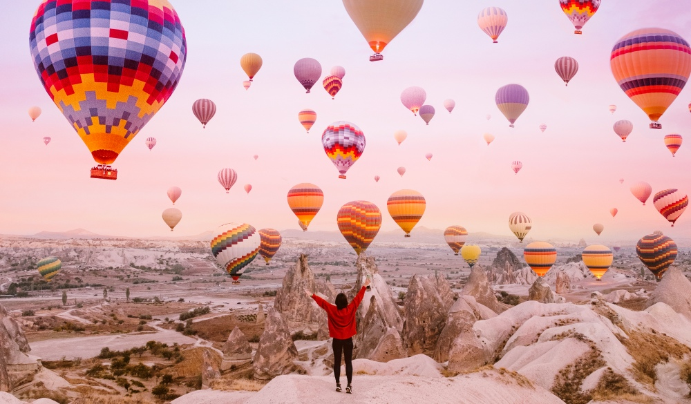 Woman watching flying balloons at sunrise in Cappadocia, ultimate travel bucket list