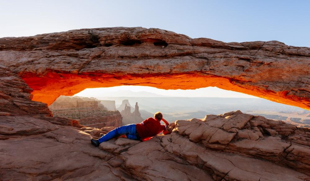Man enjoying sunrise at Mesa arch, Canyonland