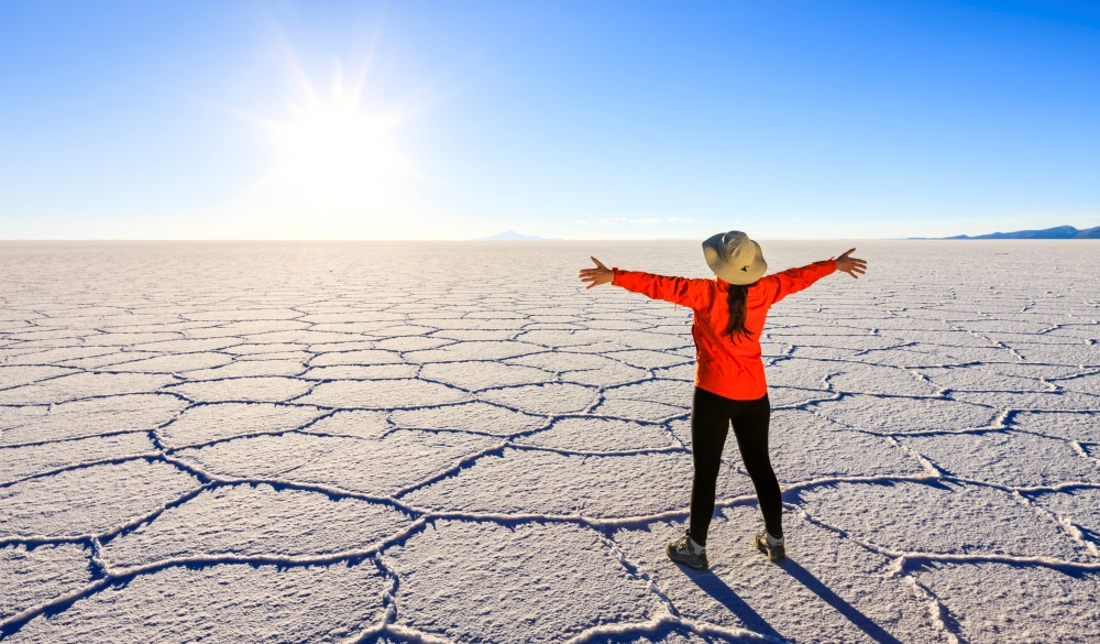 Female tourist on Salar de Uyuni, Altiplano, Bolivia, ultimate travel bucket list