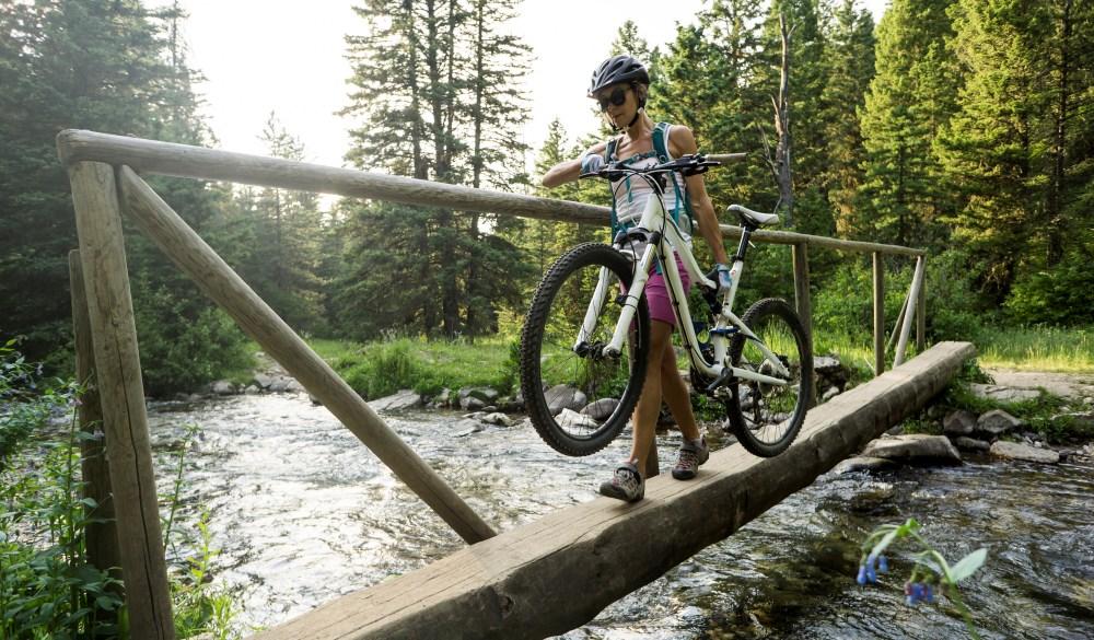 female carrying her mountain bike over a wooden bridge, bike trail