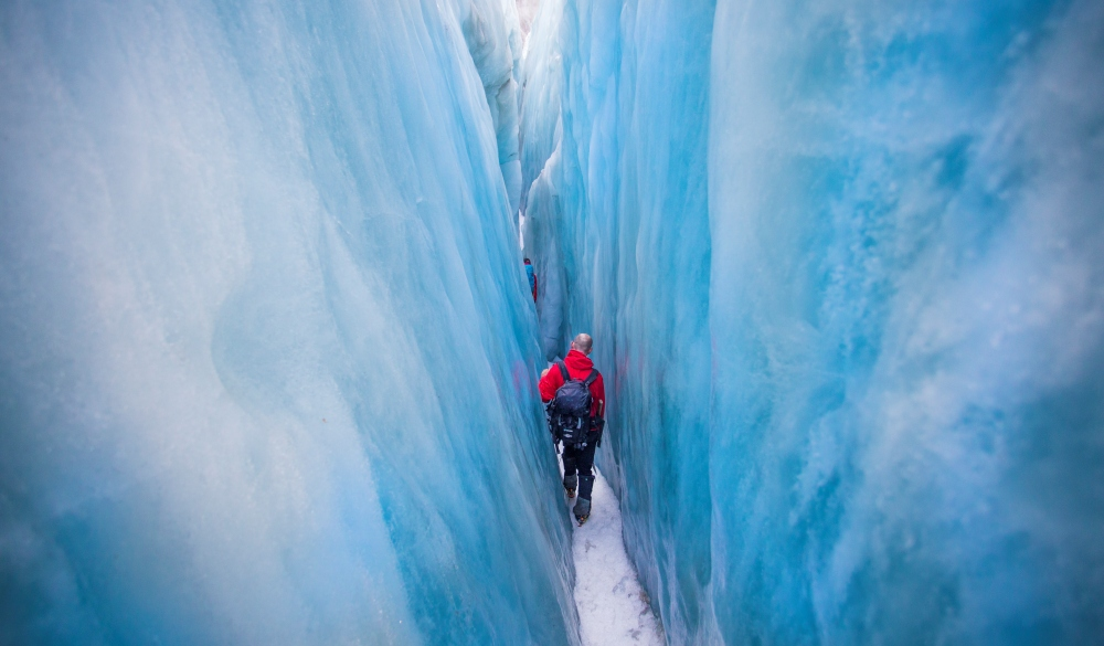 Travelers explore New Zealand's famous Franz Josef Glacier. Blue Ice, deep crevasses, caves and tunnels mark the ever changing ice. A man walks through a giant Ice crevasse, south island road trip destination