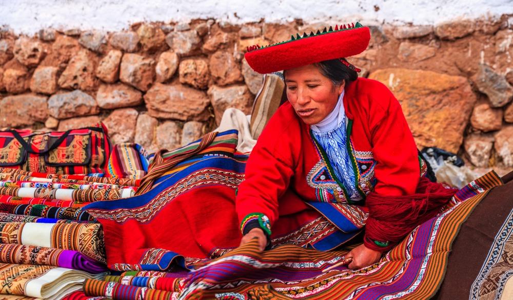 Peruvian woman selling souvenirs at Inca ruins.