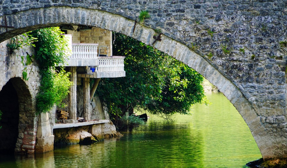 Arch Bridge Over River In Park, travel gems in europe