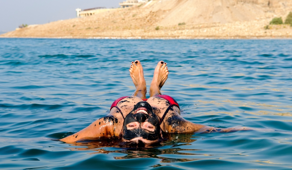 woman floating on her back in the Dead Sea after coating herself in mineral-rich mud