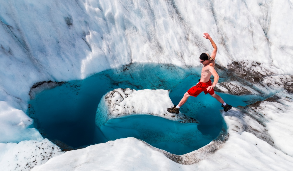 A man jumps onto an island of ice on Root Glacier in Wrangell-St. Elias National Park