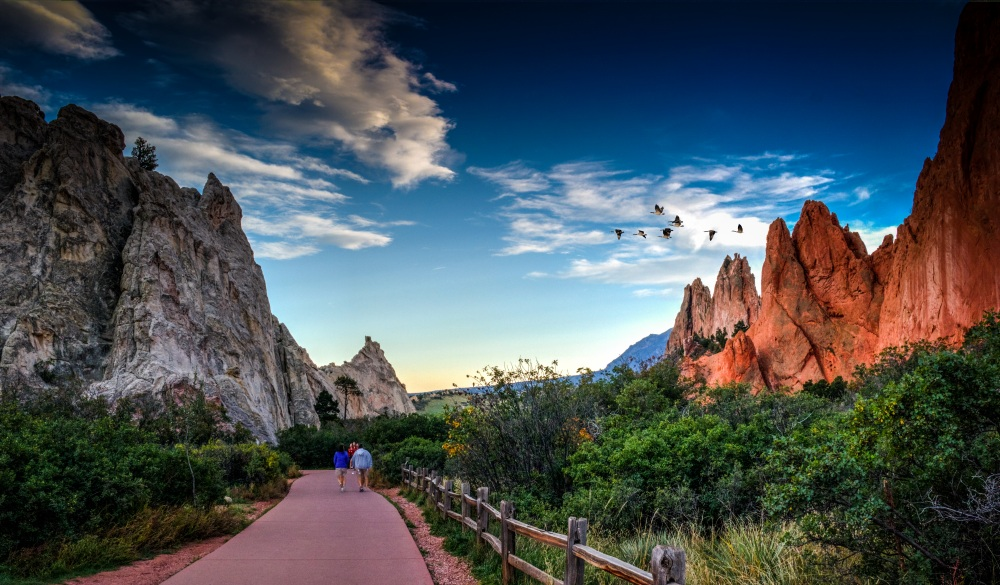 People Walking On Footpath By Rock Formation And Plants Against Sky At Colorado Springs