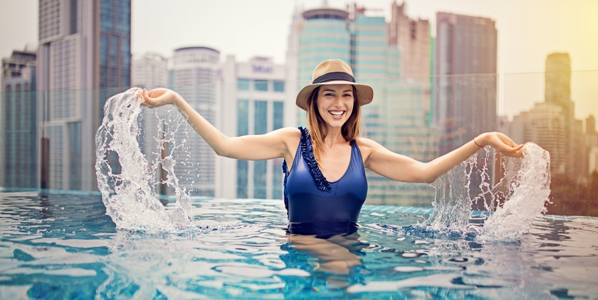 Young girl is enjoying the water on the rooftop swimming pool