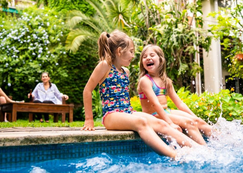 Two little girls sitting at poolside and splashing water with legs