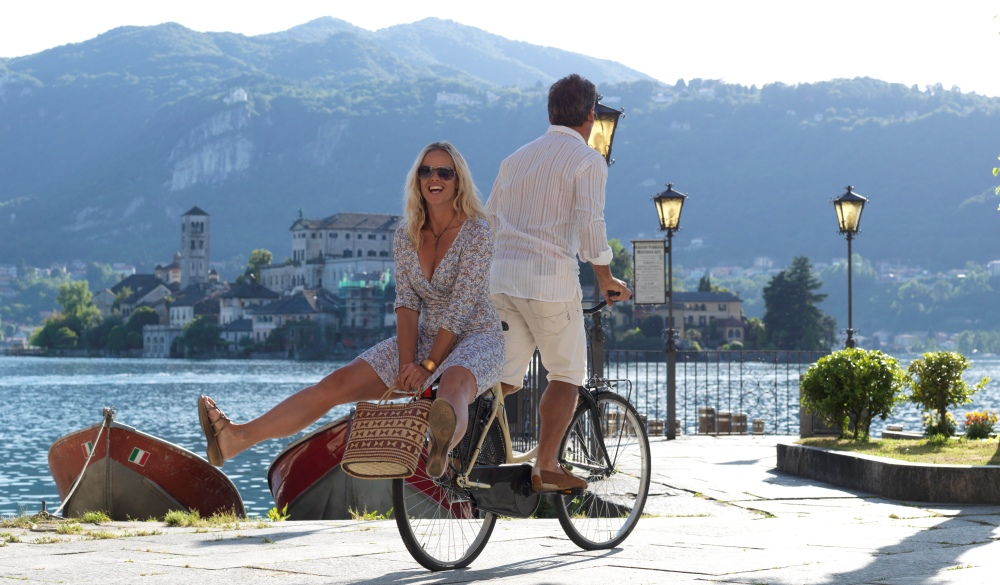Man doubles woman on cruiser bicycle, at lake