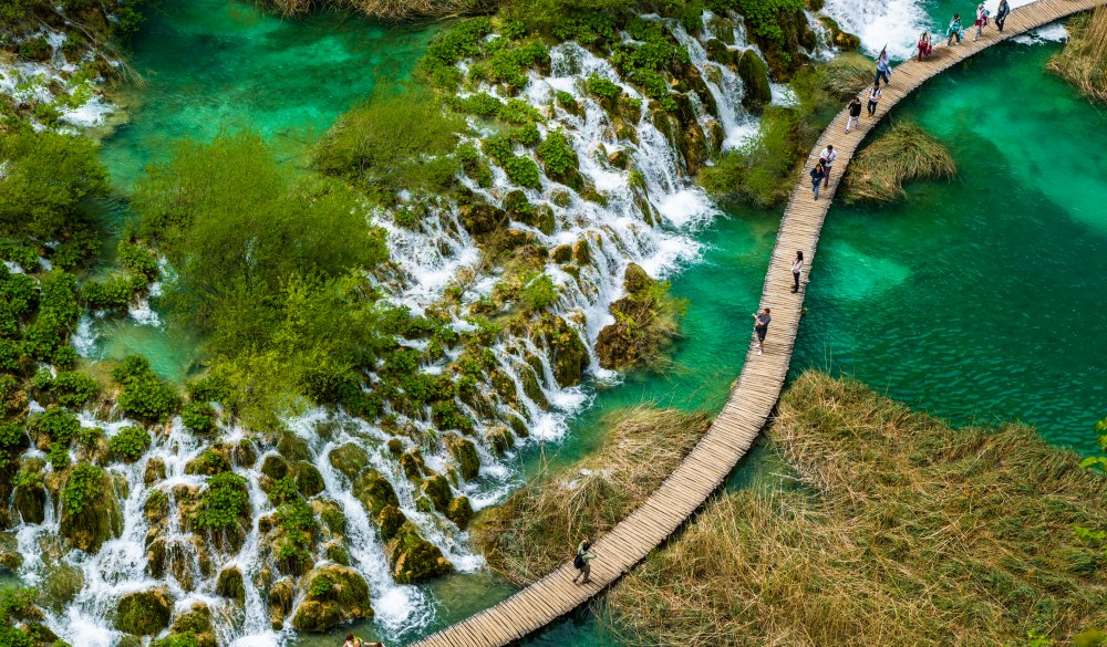 High Angle View Of People Walking On Boardwalk Over Water At Plitvice Lakes National Park, best lake getaways