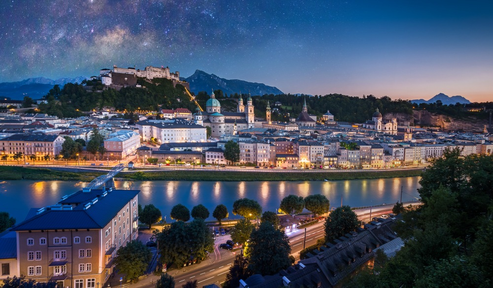 View of cityscape of Salzburg Cathedral, Fortress Hohensalzburg, and old castle in center of old town with river and road along the river at sunset time with milky way in Salzburg, Austria, Europe and also view of snow on alps mountain in background, destination for road trips in austria
