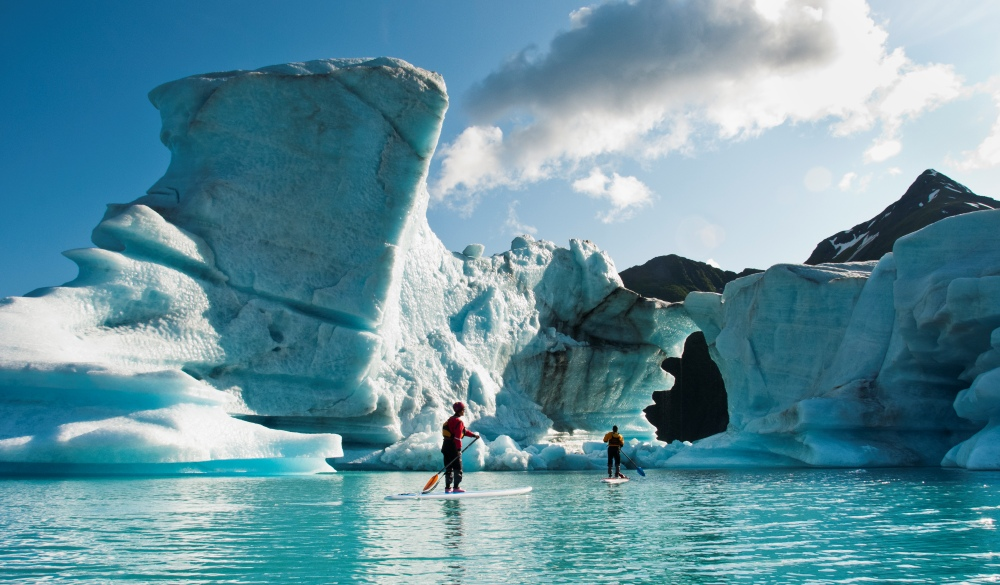 Two adults on stand up paddle board (SUP) observe hole melted in iceberg on Bear Lake in Kenai Fjords National Park, Alaska., best of Alaska