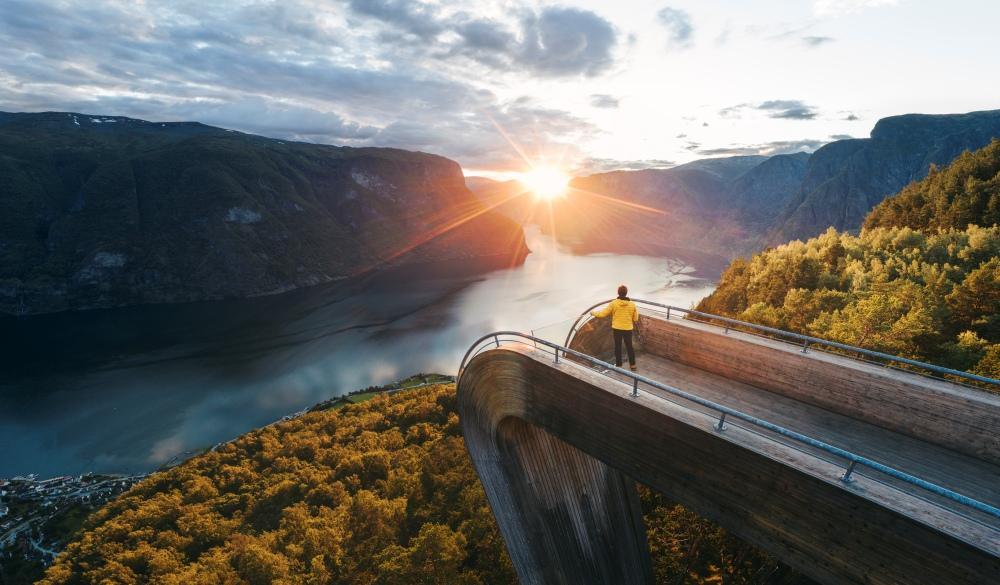 Tourist admiring the sunset over norwegian fjord, Norway, best lake getaways