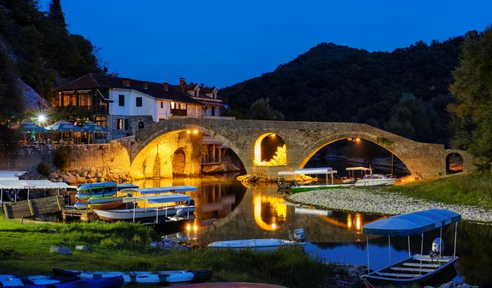 Excursion boats and Old Bridge Stari most at dusk, river Crnojevic, Rijeka Crnojevica, national park Lake Skadar, province Cetinje, Montenegro