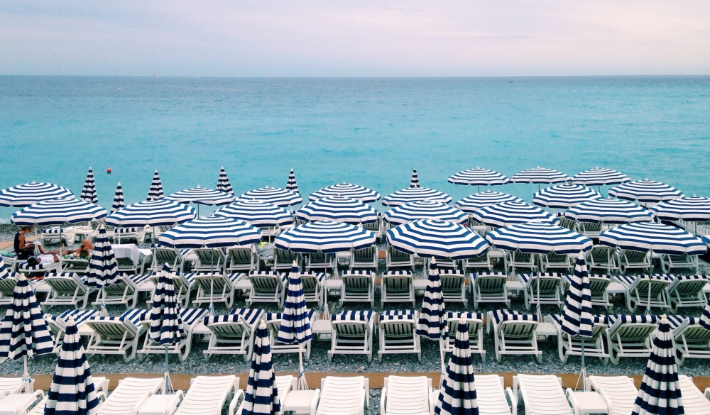 Deck Chairs And Parasols Arranged By Sea Against Sky