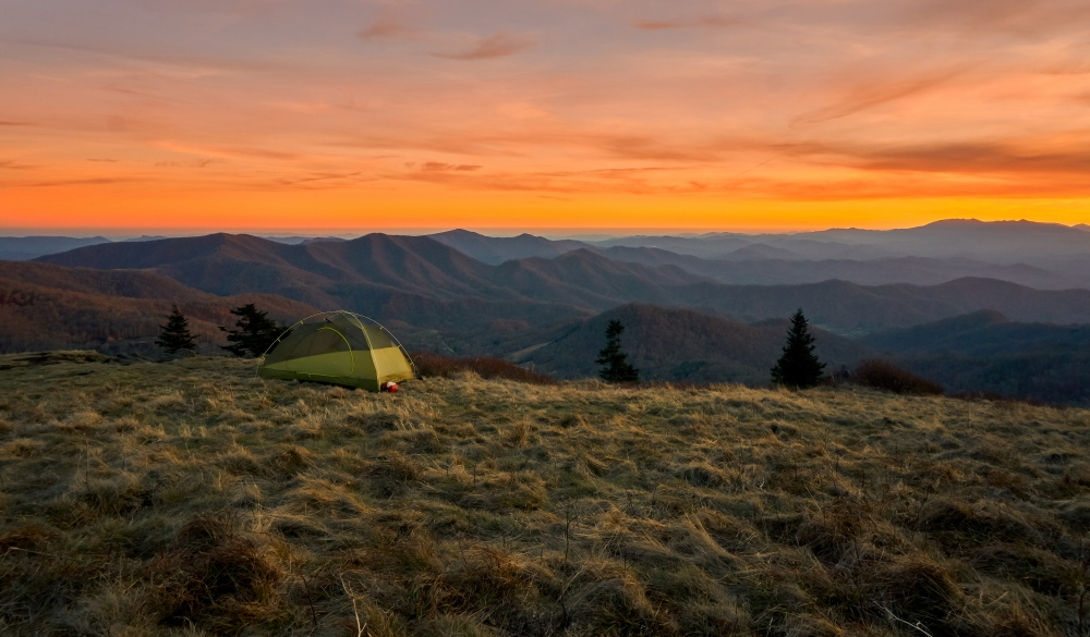Vibrantly colorful vista of a small green tent camps on a grassy bold meadow of the Appalachian Trail in the golden sunset with blue misty mountains in the background., best hikes in the US