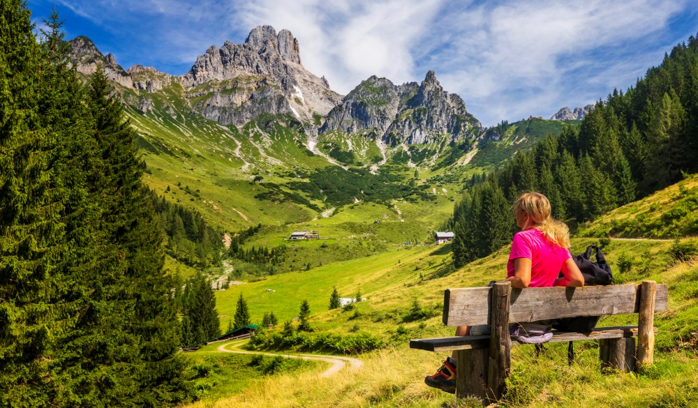 Young woman sitting on bench and enjoys view on big Bischofsmütze, Dachstein mountains, alps
