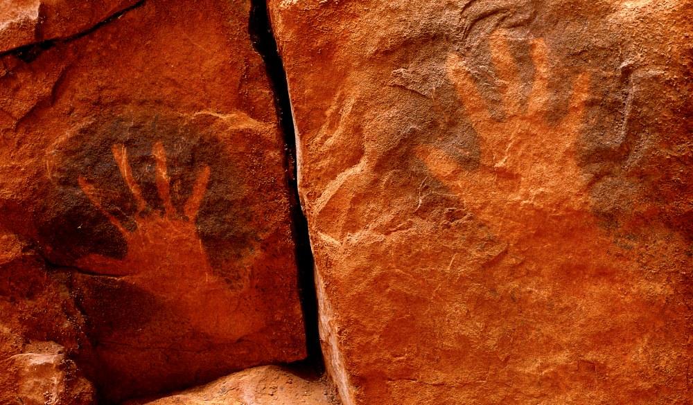 Aboriginal hand stencils on cave wall. Watarrka National Park, Northern Territory, Australia., iconic Australian road trip destinations