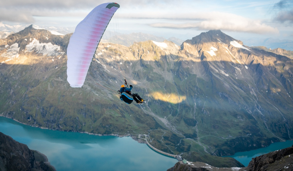 Man paragliding above alpine water reservoirs above Kaprun, Zell am See, Salzburg, Austria