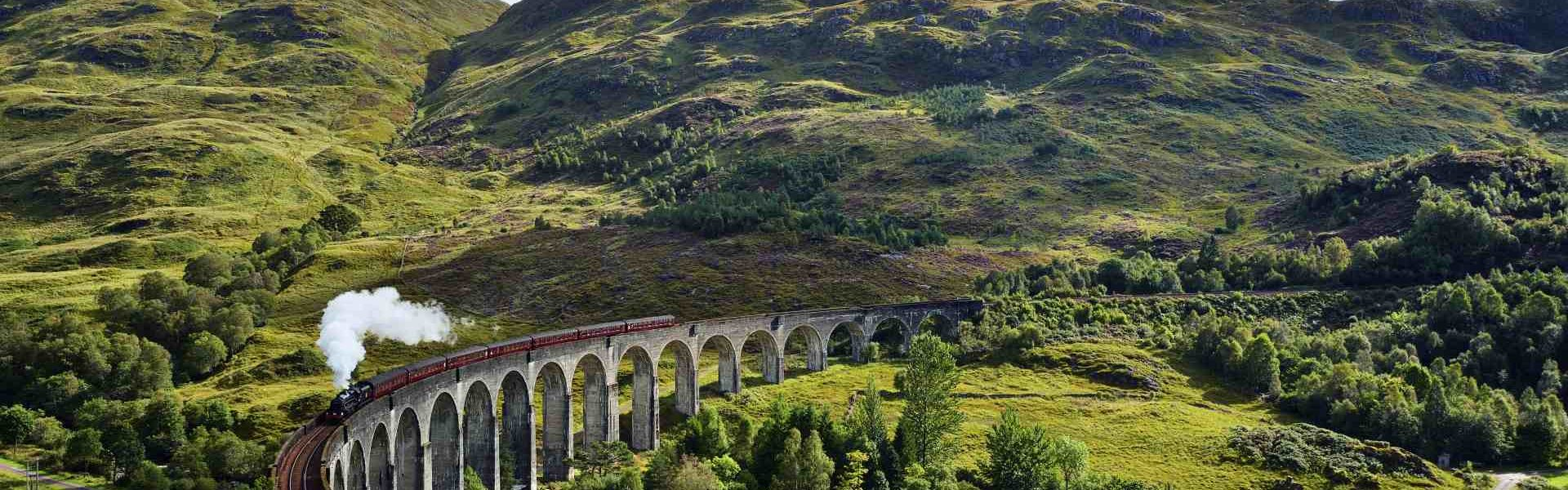 UK, Scotland, Highlands, Glenfinnan viaduct with a steam train passing over it