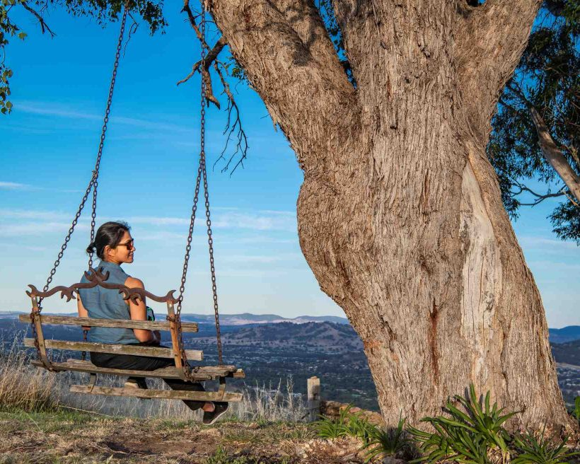 woman sitting on swing seat overlooking the bush in New South Wales