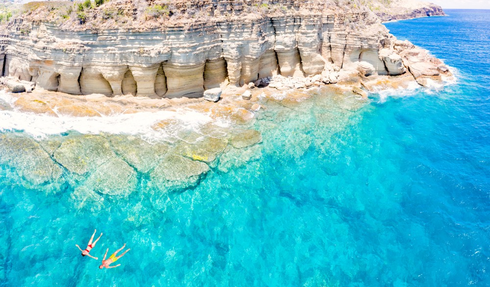 Couple floating in sea, Pillar of Hercules, Antigua, destination for a crowd-free vacation