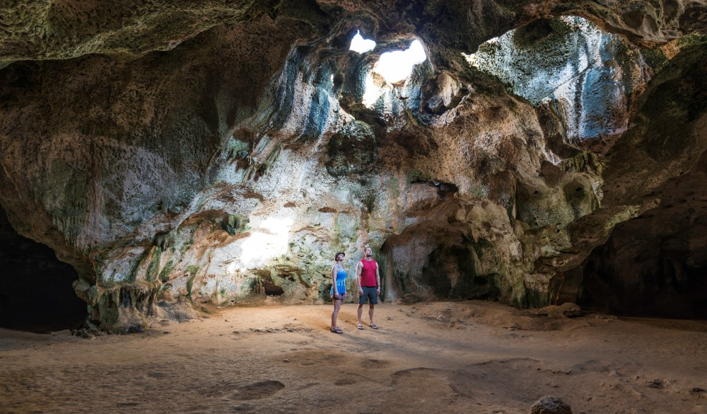 Couple discover beach passage and rock dome, destination fora crowd-free vacation