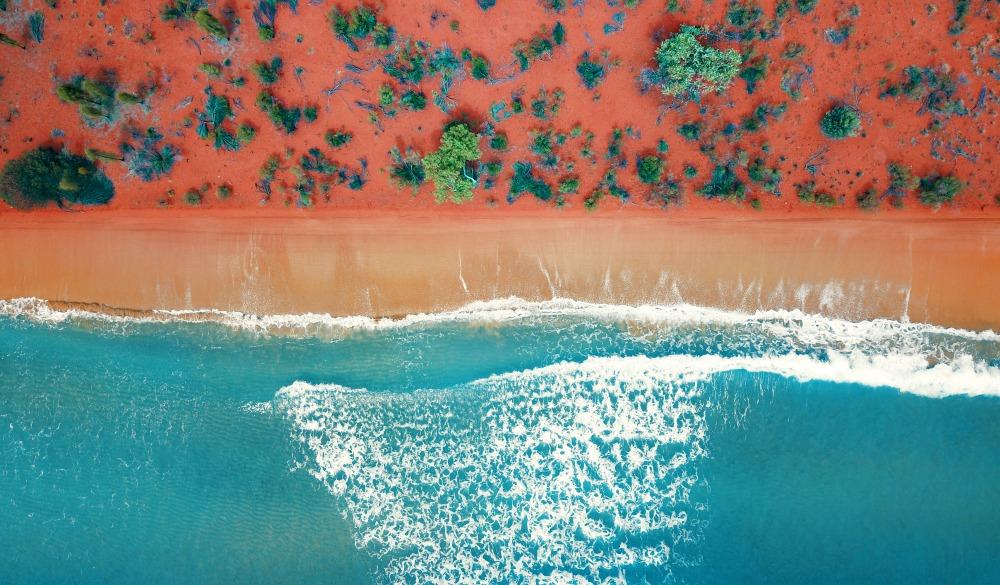 Aerial top view of a bright orange sandy beach