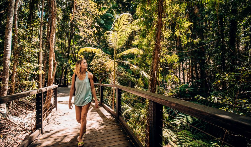 Young woman walking through the woodland area, destination for great hikes in australia