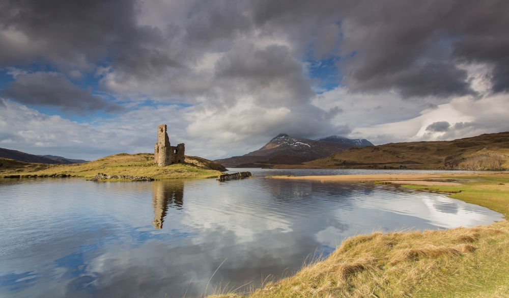 Ardvreck Castle reflected on the waters of Loch Assynt,