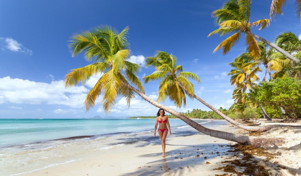 Woman in red bikini walking on tropical beach in the Caribbean