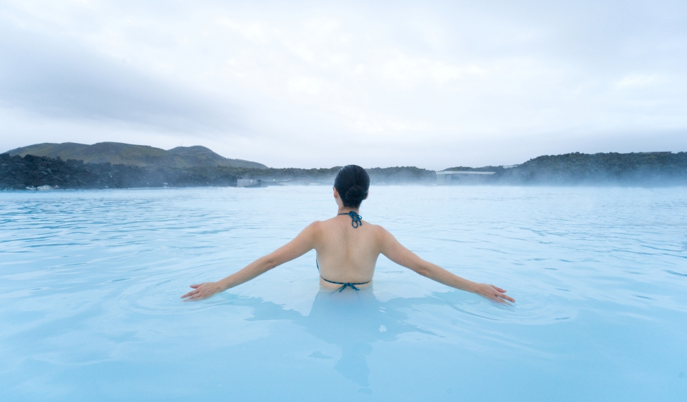 woman relaxing at the Blue Lagoon , destination for a weekend getaways in europe