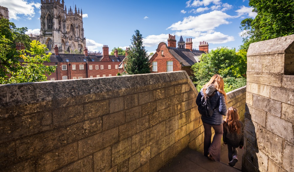 Tourists walking along York's city walls in England