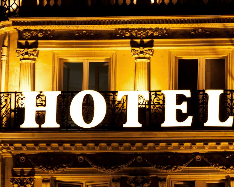 Brightly lit HOTEL sign on a hotel balcony