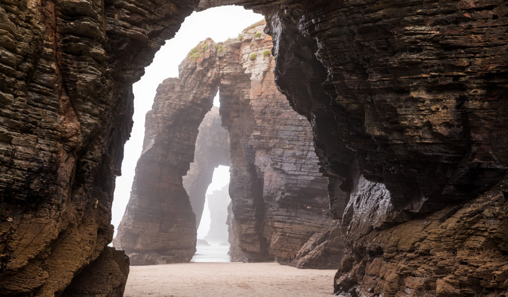 Natural rock arches on Cathedrals beach in low tide, Spain, destination for Spain road trip