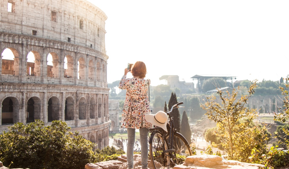 Beautiful young woman in colorful fashion dress alone on a hill with bike takes pictures of colosseum in Rome using smartphone camera at sunset. Attractive tourist girl with elegant straw hat