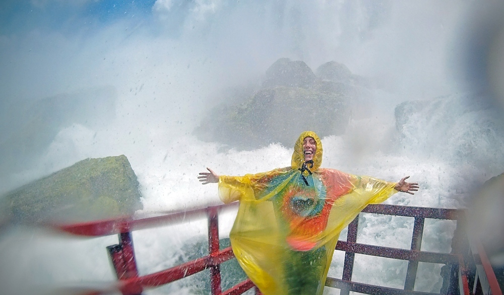 Cheerful Woman Wearing Raincoat With Arms Outstretched While Standing By Niagara Falls