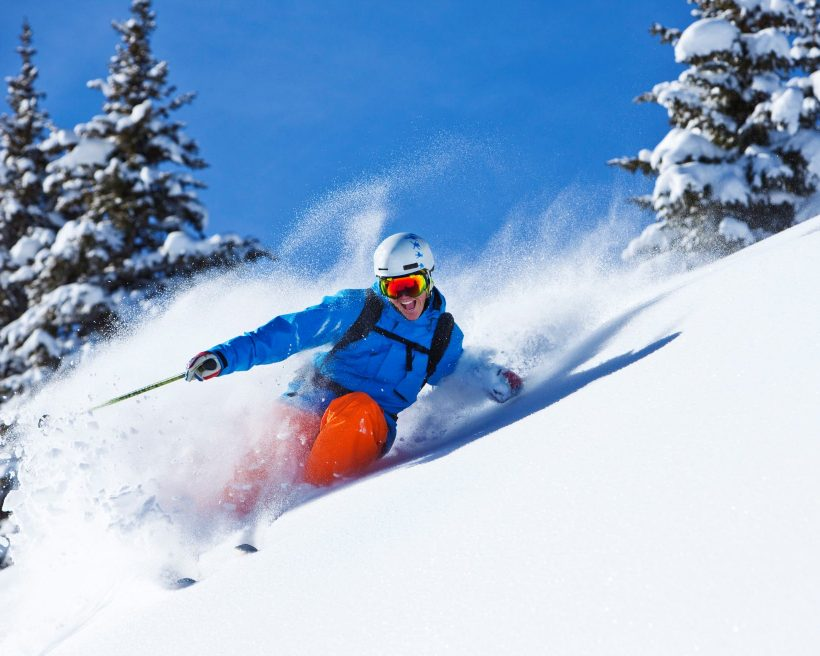 A athletic skier smiling rips fresh powder turns in the backcountry on a sunny day in Colorado.